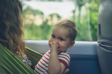 Mother with baby in sling on train