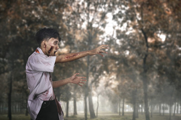 Scary asian zombie man with wounded face