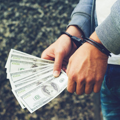 arrested rowdy in handcuffs counting dollar banknote. Arrested for attempting to bribe. Concept of crime and bribery, toned image