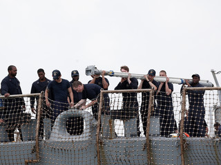 Personnel work on the U.S. Navy guided-missile destroyer USS John S. McCain after a collision, in Singapore waters