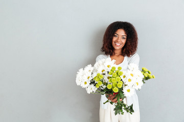 Attractive young african woman giving flower bouquet to camrera