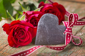 Red roses with blank slate heart and ribbon on wood  -  Birthday, Valentines day background