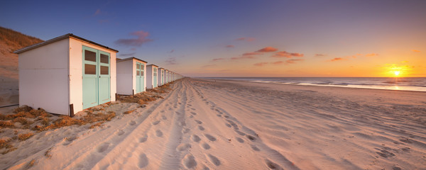 Row of beach huts at sunset, Texel island, The Netherlands Wall mural