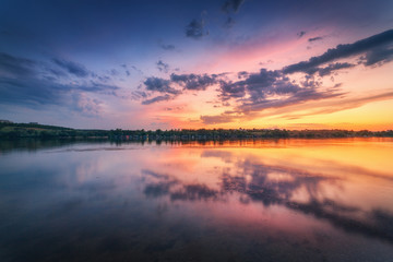 Wall Mural - Beautiful scene with river and colorful sky with clouds at sunset. Amazing landscape with lake, blue sky with multicolored clouds reflected in water at dusk. Nature background. Reflection in water
