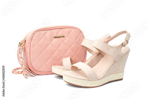 aa66c4689 Beige wedge sandal with small shoulder quilted handbag isolated on white  background