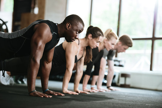 Multiethnic sports strong people make sport exercises in gym.
