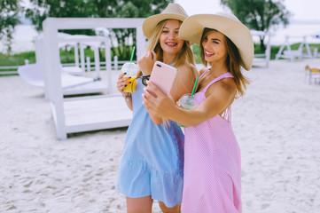 Two happy girls drink juice