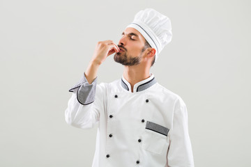 Chef is showing delicious sign on gray background.