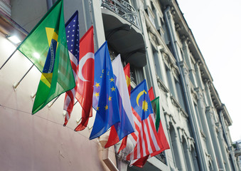 National flags of Brazil, the USA, Turkey, the European Union, Russia, China and Malaysia on the wall of the building