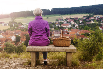 older woman sitting on bench and looking at small town