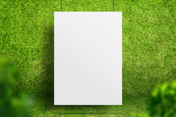 Blank white poster hanging at green grass room with blur leaf foreground,Ecology sustainable concept,Mock up for display of design