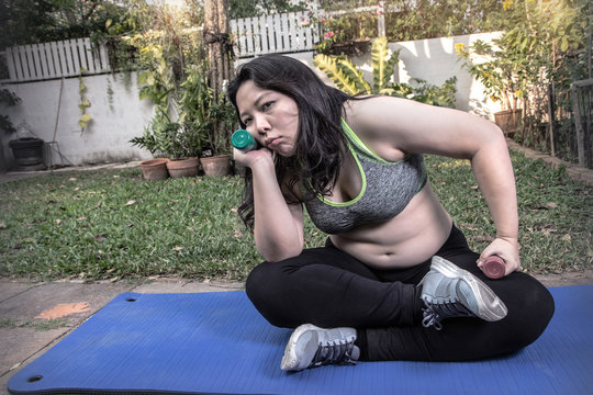 Lazy obese woman tired exercise bored face hand holding dumbbell give up workout concept