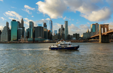 New York City, USA - August 16, 2017: American police boat N.Y.P.D patrolling under the Brooklyn Bridge