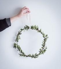 Schlichter Kranz aus Grün von einer Hand gehalten
