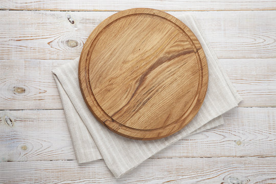 Pizza board, canvas napkin with lace on wooden table. Top view mock up