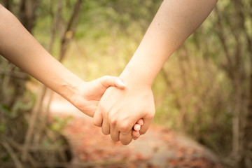 woman and man holding hands on light background, closeup