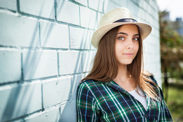 Young woman in hat leans against a blue wall