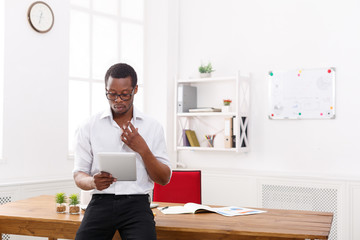 Concentrated black businessman in modern office, work with tablet