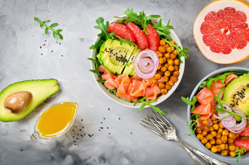Healthy salad bowl with salmon, grapefruit, spicy chickpeas, avocado, red onion and arugula