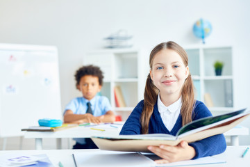 Cute schoolgirl with open book sitting at lesson of reading