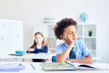 African boy daydreaming at lesson of literature and looking through classroom window