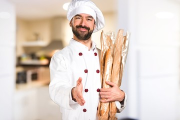 Young baker holding some bread and making a deal in the kitchen