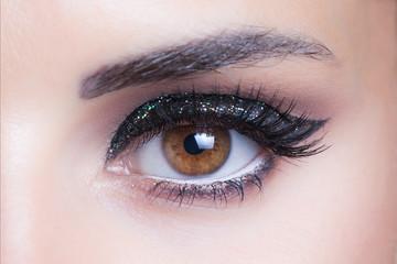 woman eye with glittering evening makeup closeup studio