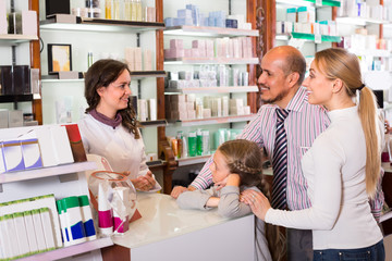 Family with a kid in pharmacy .