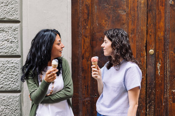 Two women friends eating ice-cream together in city during summer