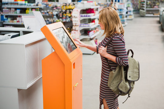 A woman chooses the goods online at the self-service device in hardware store