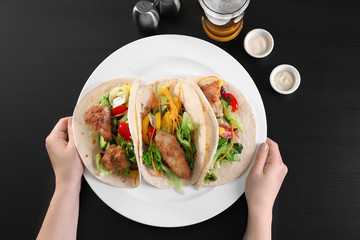 Hands holding plate with delicious fish tacos on black background