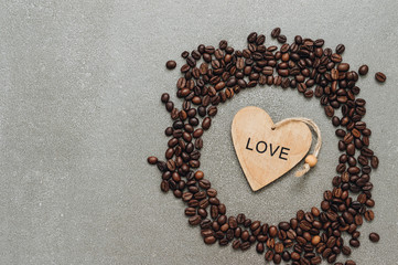 Grains of coffee and wooden heart on a gray background, top view.