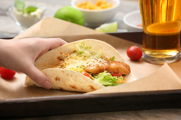 Hand taking delicious fish taco from tray