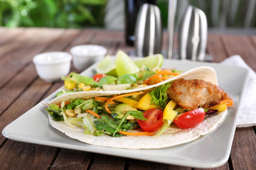 Delicious fish taco served on white plate on wooden table