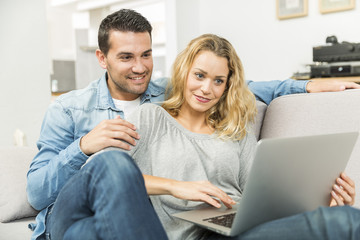 Young couple making the most of new technologies in their house