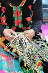 Hands of woman showing weaving action of traditional bamboo basket from the Kadazan Dusun Murut ethnic of Sabah Borneo, Malaysia.