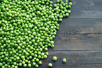 Green peas on a wooden surface, top view. Textural background