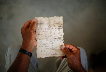 Palestinian fisherman Jihad al-Soltan displays a message that was written by Bethany Wright and her boyfriend Zac Marriner, after he found it in a bottle off a Gaza beach, in Gaza