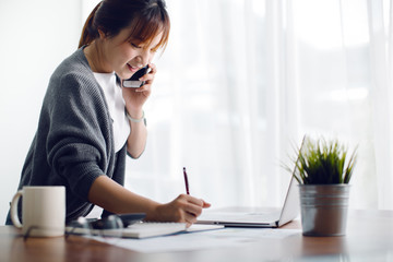 Young Asia woman working with smart phone and laptop in the office