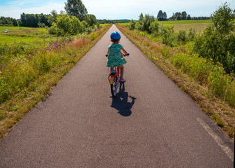 Back view of little girl on the bike in Swedish landscape