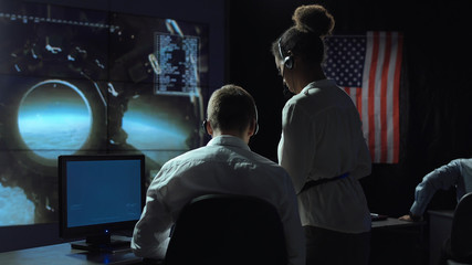 Back view of man and woman in space flight control center. Moon landing of spaceship module.