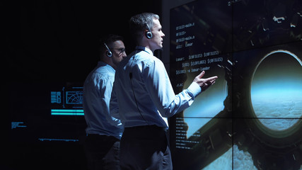 Back view of two supervisors standing at screen in space center and controlling landing on Moon.