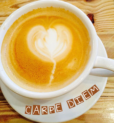 Inspirational Quote:  Carpe Diem:  Seize the Day with coffee cup and saucer filled wth latte and froth in the shape of a heart