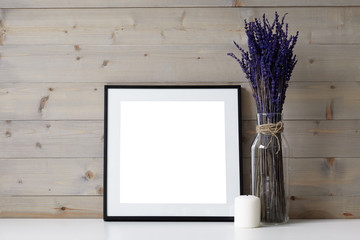 Close up picture of foursquare space photo frame with copy space, white paraffin candle and glass vase with dried lavender flowers in it. Ideas for interior, decor, decoration and design concept