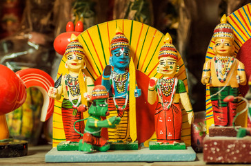 Lord Krishna and servants in forms of colorful wooden toys in traditional style of India, in showcase of indian store
