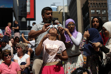 A girl views the solar eclipse at Times Square in Manhattan, New York