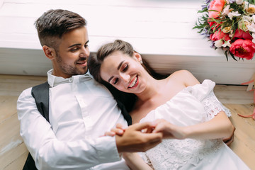 Cheerful newlyweds holding hands and lie on the floor next to bridal bouquet. Artwork. Wedding morning. Soft focus
