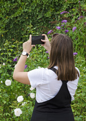 Young girl with mobile phone photographing green garden, with white shirt and watch and skirt