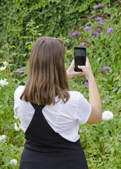 Young girl with mobile phone photographing green garden, with hands and white watch and skirt