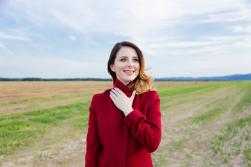 Woman in red coat at countryside field